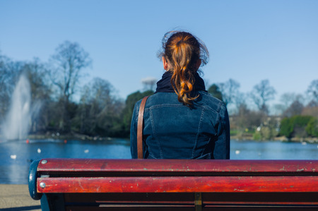 A young woman is sitting on a park bench by a pond photo