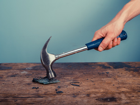 smashing: A hand is smashing a computer chip on a wooden desk with a hammer Stock Photo