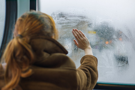 A young woman is wiping the dew off a window in a bus Stock Photo