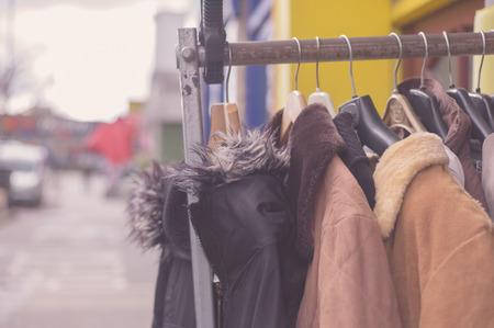 A bunch of winter jackets hanging on a rail outside Foto de archivo