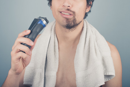 A young man cannot finish shaving because his electric razor is broken photo