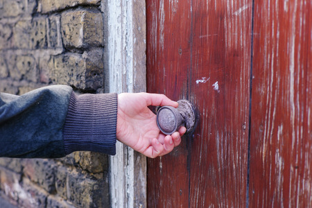 iron gate: A female hand is touching and feeling a nice old knob on a rustic door