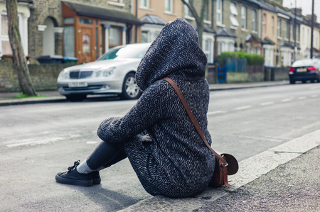 kerb: A young woman is sitting in the street on the kerb Stock Photo