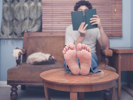 pies masculinos: Un joven descalzo está descansando sus piernas sobre una mesa de café en el país durante la lectura, hay un gato en el sofá junto a él