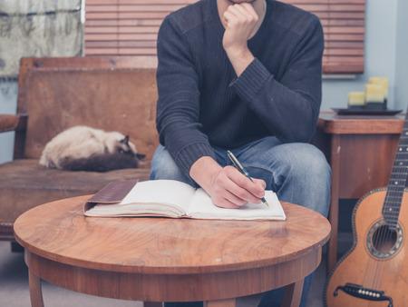 hombre escribiendo: Un joven est� sentado con su gato y guitarra en su casa en un sof� y est� escribiendo canciones en un cuaderno Foto de archivo