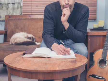 A young man is sitting with his cat and guitar at home on a sofa and is writing songs in a notebook
