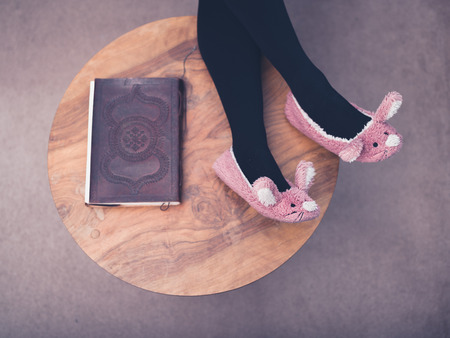 The feet and legs of a young woman wearing bunny slippers and resting her feet on a coffee table