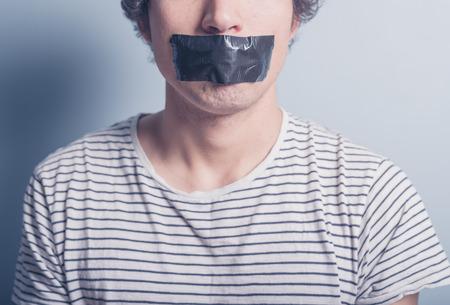 boca: Un joven tiene un gran trozo de cinta industrial negro que cubre su boca