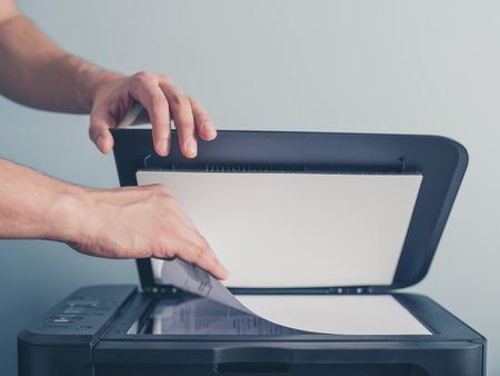impresora: Las manos de un hombre joven se placeing un pedazo de papel en un escáner plano en preparado para copiarlo