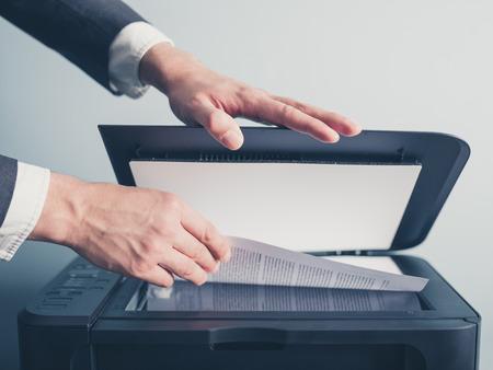 impresora: Las manos de un joven empresario está placeing un documento en un escáner de superficie plana en preparado para copiarlo