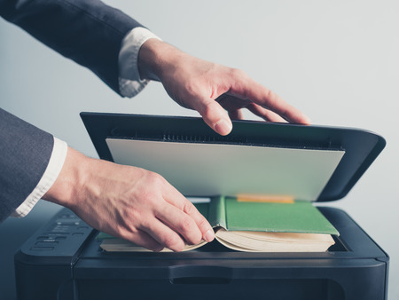 preperation: The hands of a young businessman is placeing a book on a flatbed scanner in preperation for copying it