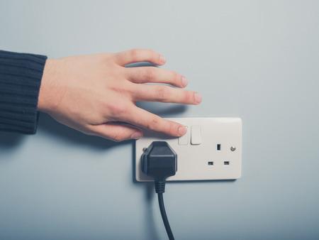 男性の手は壁のコンセントにスイッチを押すこと