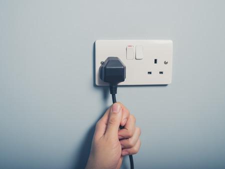 Mężczyzna ręka ciągnie niego przewód elektryczny podłączony do gniazdka w ścianie Zdjęcie Seryjne