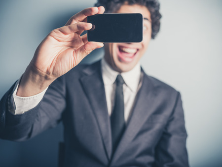 funny guys: A young busnessman is using his smartphone to take a selfie Stock Photo