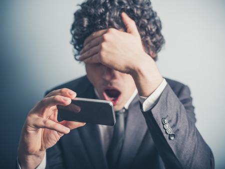 sorpresa: Un joven empresario es sorprendido por algo en su smartphone