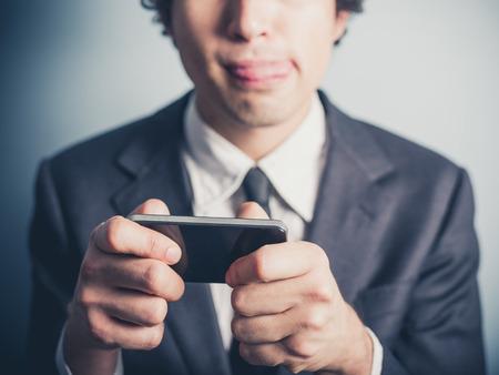 青年実業家は彼のスマート フォンにモバイル ゲームをプレイします。