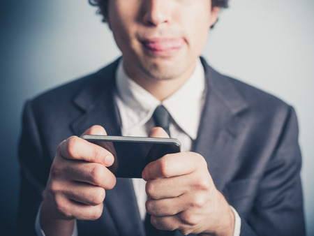 A young businessman is playing mobile games on his smartphone Stock Photo