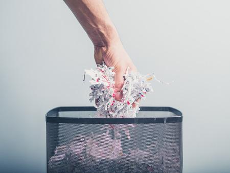 手は、廃棄物の紙の籠に細断紙の束を入れています。