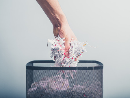 A hand is putting a bunch of shredded paper in a waste paper basket Standard-Bild