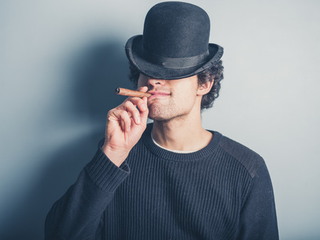 bowler hat: A happy young man wearing a black sweater and a bowler hat is smoking a cigar Stock Photo