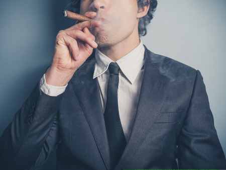 smoking a cigar: A young confident businessman is smoking a cigar