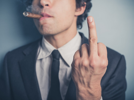 A young businessman is smoking a cigar and is displaying a rude gesture