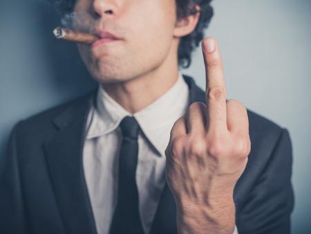 arrogancia: Un joven empresario está fumando un cigarro y está mostrando un gesto grosero Foto de archivo