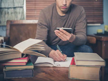 A young man is sitting on a sofa surrounded by books and is using his smartphone
