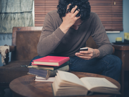 A young man surrounded by books is sitting on a sofa and is looking upset as he is using his smartphone