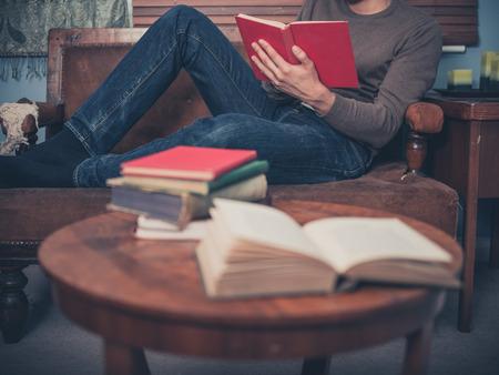 若い男は、自宅のソファでリラックスと本を読んでいます。 写真素材