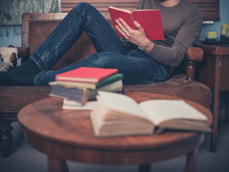 A young man is relaxing on a sofa at home and is reading a book