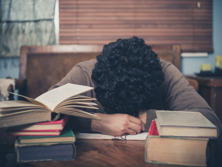 tired: A tired student is asleep with his head on a coffee table surrounded by books