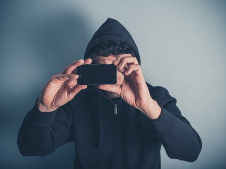 documenting: A young man wearing a hooded top is taking photos with his smartphone
