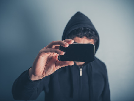 hooded top: A young man wearing a hooded top is taking photos with his smartphone