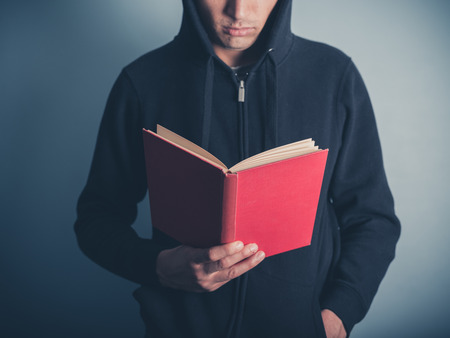 hooded top: A young man wearing a hooded top is standing around and is reading a red book