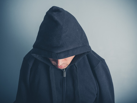 A young man is wearing a hooded top and is looking down photo