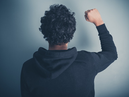 hooded top: Rear view shot of a young man in a hooded top raising his fist in the air