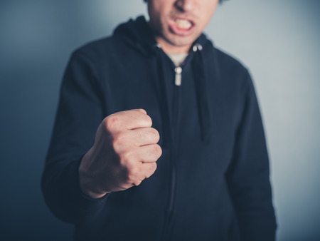 angry: Close up on a young man raising his fist