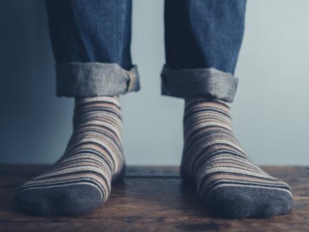 pies masculinos: Los pies de un hombre de pie sobre un suelo de madera que llevan calcetines a rayas Foto de archivo