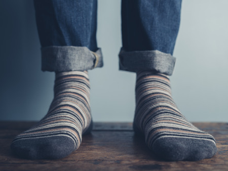 The feet of a man standing on a wooden floors wearing stripey socks Stock Photo