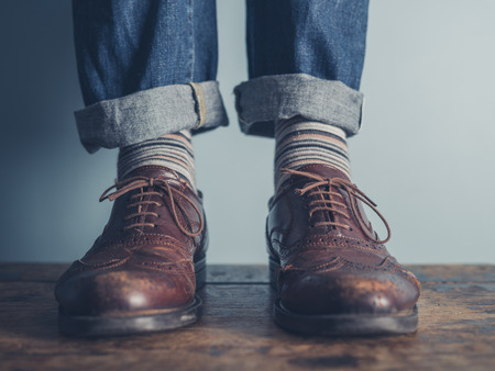 The feet of a man standing on a wooden floors wearing stripey socks and leather shoes