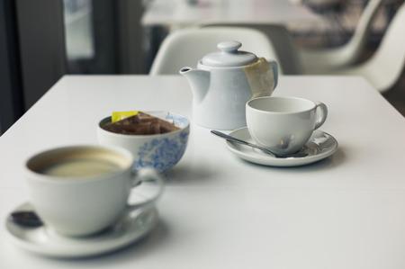sachets: Una tetera y dos tazas en una mesa en un caf�