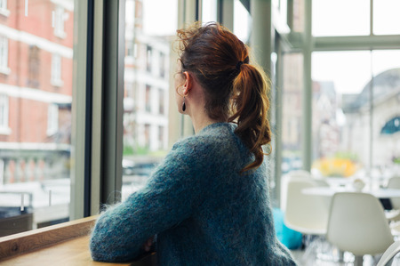 speculating: A young woman is sitting by the window and is looking out