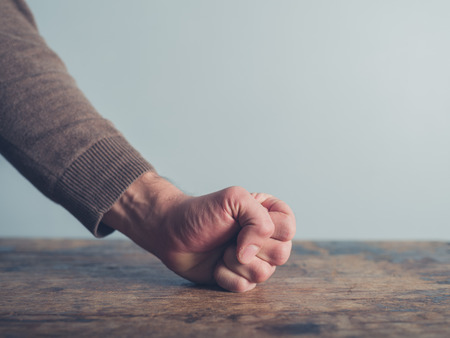 puños cerrados: Primer en un hombre golpeando el puño sobre una mesa de madera