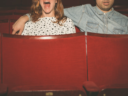 scared woman: A young couple is watching a film in a movie theater, the woman is scared but her partner is looking relaxed Stock Photo