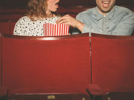 sgomento: Una giovane coppia sta guardando un film in un cinema e l'uomo sta rubando popcorn della donna al suo sgomento Archivio Fotografico