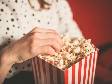 Close-up op een jonge vrouw het eten van popcorn in een bioscoop