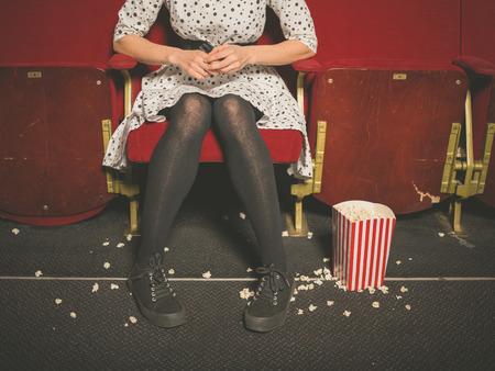 若い女性は床に座ってポップコーン映画館で