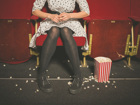 theater seat: A young woman is sitting in a movie theater with popcorn on the floor
