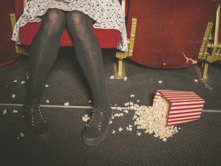 palomitas de maiz: Una mujer joven está sentado en una sala de cine con un cubo de palomitas de maíz derramado en el suelo delante de ella
